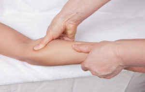 therapist massages to sooth pain in the forearm