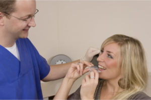 The dentist gives the custom made mouth guard to his patient.
